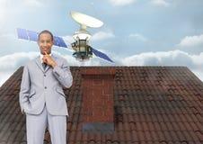 Спутниковый плавать и бизнесмен стоя на крыше с печной трубой и небом стоковые фото