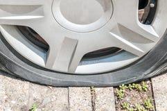 Спущенная шина на колесе автомобиля припаркованного на конце улицы вверх Стоковые Изображения