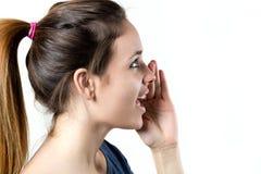 Сплетня молодой белокурой женщины шепча Стоковое Фото
