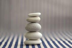 Сработанность и баланс, пирамида из камней утеса камешка, простые камни выправки на белой и голубой striped предпосылке, скульпту стоковые изображения