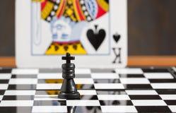 Сравнение черного короля шахмат с пиком карточки Стоковые Фотографии RF
