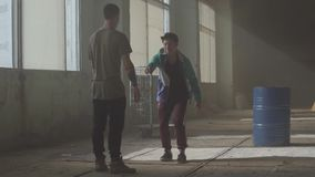 Сражение танца 2 танцоров улицы в получившемся отказ здании около бочонка Тазобедренная культура хмеля Репетиция Сверстница видеоматериал