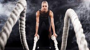 Сражение ropes встреча Привлекательные детеныши приспосабливать и тонизировали спортсменку разрабатывая в функциональном спортзал Стоковое фото RF