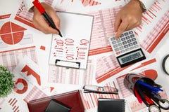 Сразу над взглядом бизнесмена работая и высчитывая финансы, читает и пишет отчеты Финансовый учет дела стоковая фотография