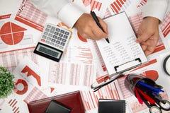 Сразу над взглядом бизнесмена работая и высчитывая финансы, читает и пишет отчеты Финансовый учет дела стоковые изображения rf