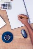 Сразу над съемкой сочинительства бизнесмена на тетради кофе на столе Стоковые Фото