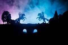 Средневековая батальная сцена на мосте с кавалерией и пехотой Силуэты диаграмм как отдельные объекты, бой между ратниками на d стоковые фотографии rf