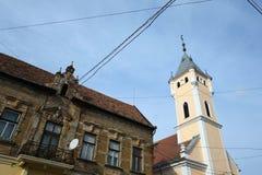 Средневековая католическая церковь около старого украшенного здания Стоковые Фото