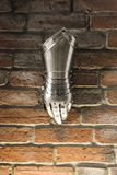 Средневековая перчатка металла, деталь части старого панцыря, деталь войны Светя перчатка утюга против предпосылки кирпичной стен стоковая фотография rf