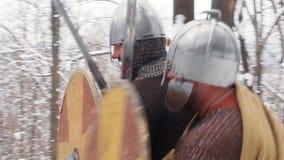 Средневековое frankish, ирландский, ратники Викинга в панцыре воюя в лесе зимы с экранами шпаг видеоматериал