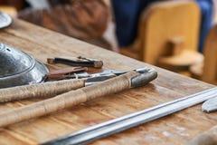 Средневековые железные оружия клали вне на деревянный стол Стоковое Изображение RF