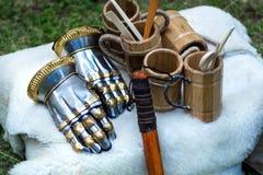 Средневековые перчатки руки металла рыцаря и деревянная чашка для питья на белом одеяле меха стоковое изображение
