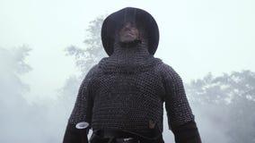 Средневековый солдат в панцыре chainmail и со шлемом на его голове в дожде сток-видео