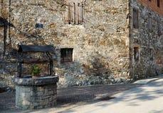 Средневековый хорошо с старым каменным зданием на предпосылке Стоковая Фотография