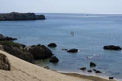 Среднеземноморское побережье с неопознанными туристами включило standup paddleboarding Стоковое Изображение