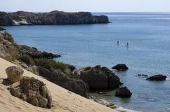 Среднеземноморское побережье с неопознанными туристами включило standup paddleboarding Стоковая Фотография