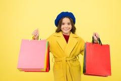 СРЕДНЕСПЕЛАЯ ПРОДАЖА Хозяйственные сумки владением ребенк девушки милые на желтой предпосылке Магазин с картой скидки Получите по стоковые фото