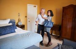 Средние достигшие возраста пары обнимая смотреть вокруг их гостиничного номера стоковое фото