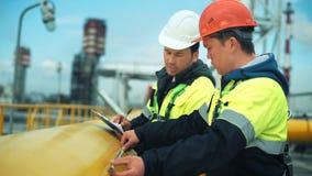Средние работники конца-вверх в производственной установке работая на нефтепроводе измерения проверки команды акции видеоматериалы