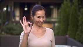 Средний достигший возраста азиатский знак ок показа женщины снаружи акции видеоматериалы