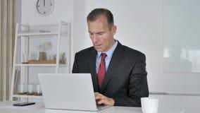 Средний достигший возраста бизнесмен кашляя на работе, кашель и горло витают сток-видео