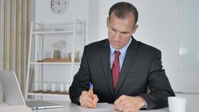 Средний достигший возраста бизнесмен писать документы в офисе акции видеоматериалы