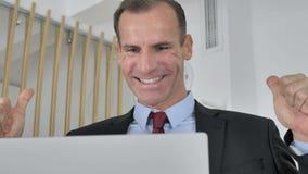 Средний достигший возраста бизнесмен празднуя успех, работая на ноутбуке