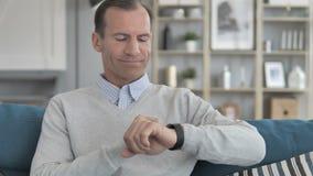 Средний достигший возраста человек ослабляя на кресле и используя применения Smartwatch акции видеоматериалы