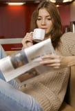 Средний кофе взрослой женщины выпивая и весточка читать стоковая фотография