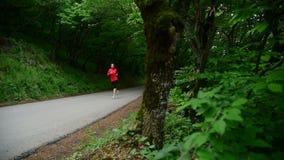 Средний общий план Милая девушка Белокурая девушка в наушниках бежит за камерой в взгляде со стороны леса видеоматериал