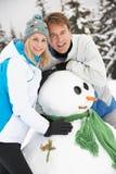 Средний постаретый снеговик здания пар на празднике лыжи Стоковые Фотографии RF