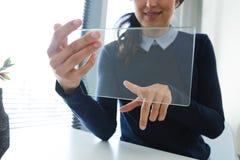 Средний раздел женской исполнительной власти используя стеклянную цифровую таблетку на столе Стоковые Фотографии RF