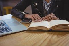 Средний раздел женщины с книгой в кафе Стоковые Изображения