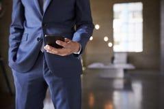 Средний раздел человека в голубом костюме используя smartphone, конец вверх стоковое изображение