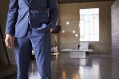 Средний раздел человека в голубом положении костюма, руке в карманн стоковые фото