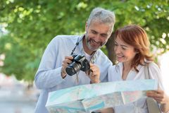 2 средних взрослых туриста идя через парк, женщина держат карту и человек показывает изображения на цифровой фотокамере стоковая фотография rf