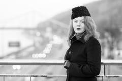 Средняя достигшая возраста женщина в черном пальто на мосте женщина портрета урбанская стоковая фотография