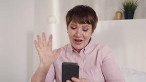Средняя достигшая возраста женщина используя телефон для онлайн болтовни сток-видео