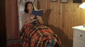 Средняя достигшая возраста женщина читая книгу в кресле с шотландкой сток-видео