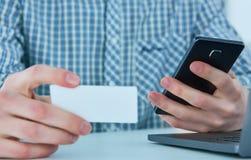 Средняя секция молодого бизнесмена говоря на телефоне и держа визитную карточку на рабочем месте Стоковая Фотография RF