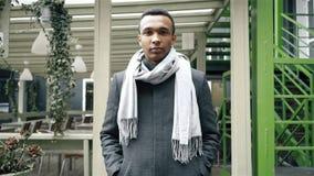Средняя съемка красивого Афро-американского человека который носит пальто и шарф Handheld съемка портрета замедленного движения сток-видео