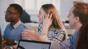 Средняя съемка молодой счастливой многонациональной команды деловых партнеров говоря, усмехаясь на методе мозгового штурма за таб видеоматериал