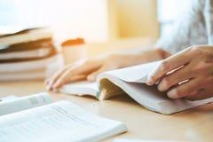 Средняя школа или студенты колледжа изучая и читая в библиотеке стоковое фото rf