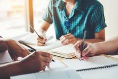 Средняя школа или студенты колледжа изучая и читая совместно внутри Стоковое фото RF