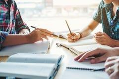 Средняя школа или студенты колледжа изучая и читая совместно внутри стоковое фото