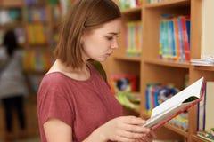 Средняя школа, образование и концепция учить Девушка студента с качанным стилем причесок, одетым в случайной футболке, владения р стоковые фото