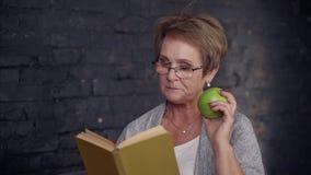 Средн-достигшая возраста женщина есть яблоко и книгу чтения дома акции видеоматериалы