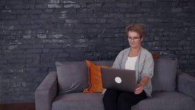 Средн-достигшая возраста женщина используя ее ноутбук дома видеоматериал
