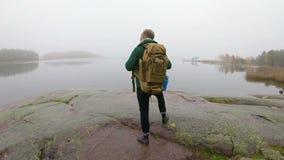 Средн-достигшая возраста живая природа человека наблюдая через бинокли на скалистом береге моря на туманном утре осени акции видеоматериалы
