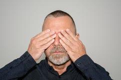Средн-достигший возраста бородатый человек покрывая его глаза стоковая фотография rf